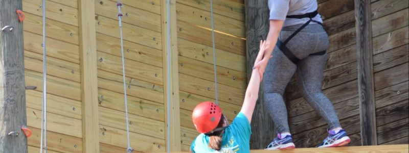 Lead & Serve TC students giving each other a hand on the high ropes course