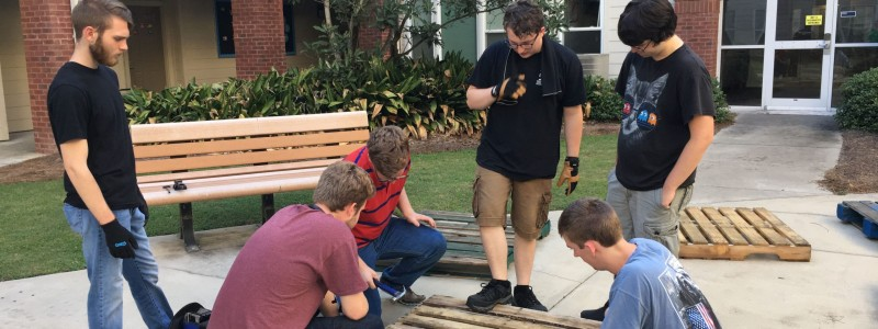 Innovation LLC students building a chair for the Greenfest Pallet Challenge